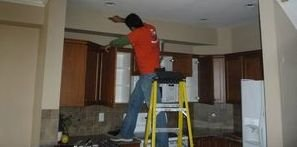 Water Damage Restoration Tech Conducting Ceiling Repair
